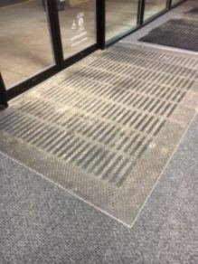 Carpeted entry mat that is very dirty.