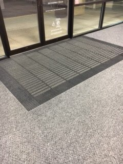 Carpeted entry mat just inside of glass doors.