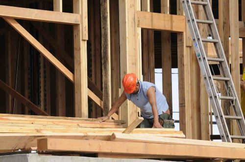 Construction site framing a building with wood and a man in a red hard hat.